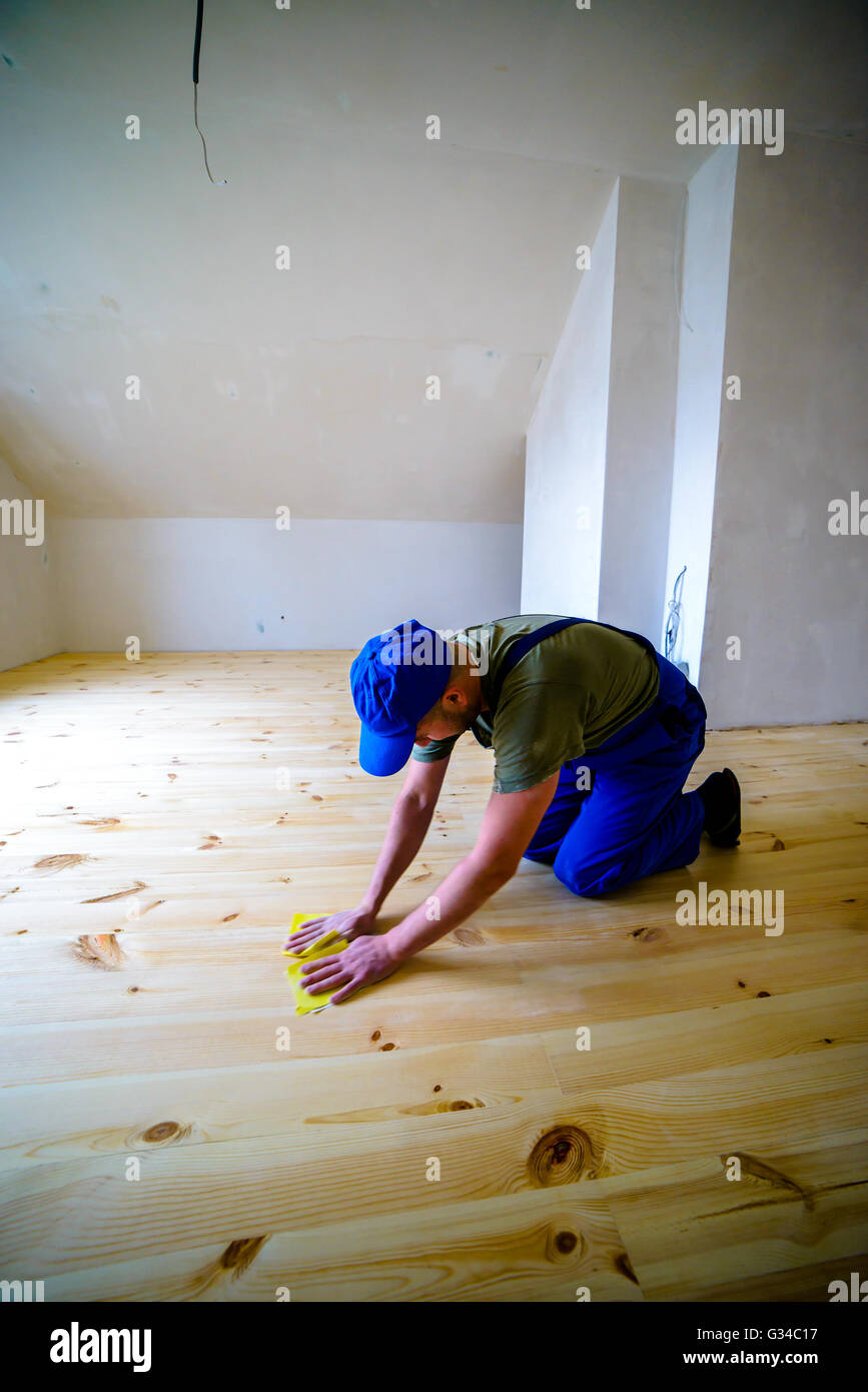 Wooden floor polishing, before varnished.Worker with emery. - Stock Image