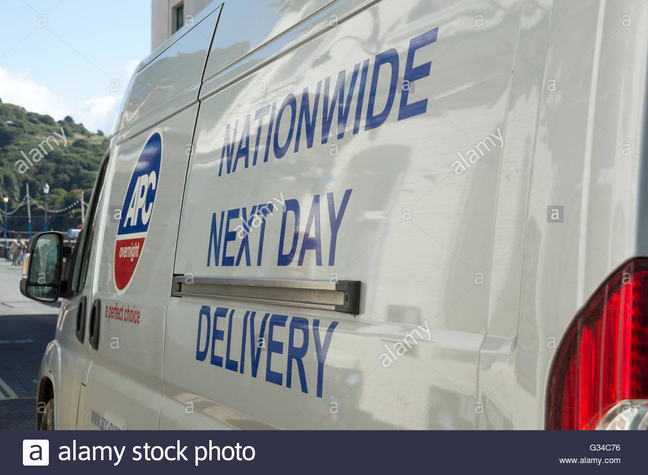 Close-up of the side of a white van advertising APC Nationwide Next Day Delivery - Stock Image