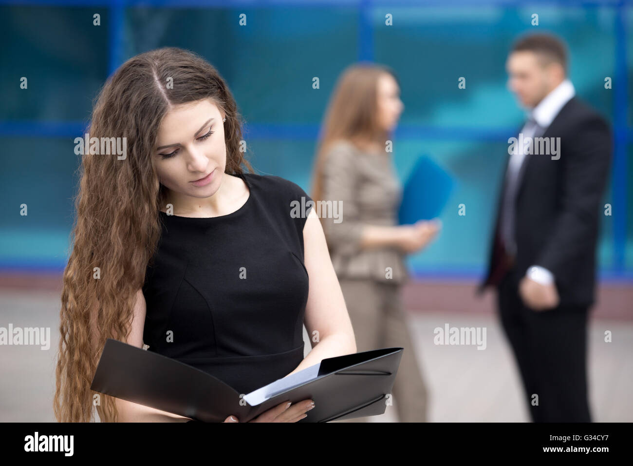 Portrait of confident young woman looking through documents with serious facial expression outdoors. Successful - Stock Image