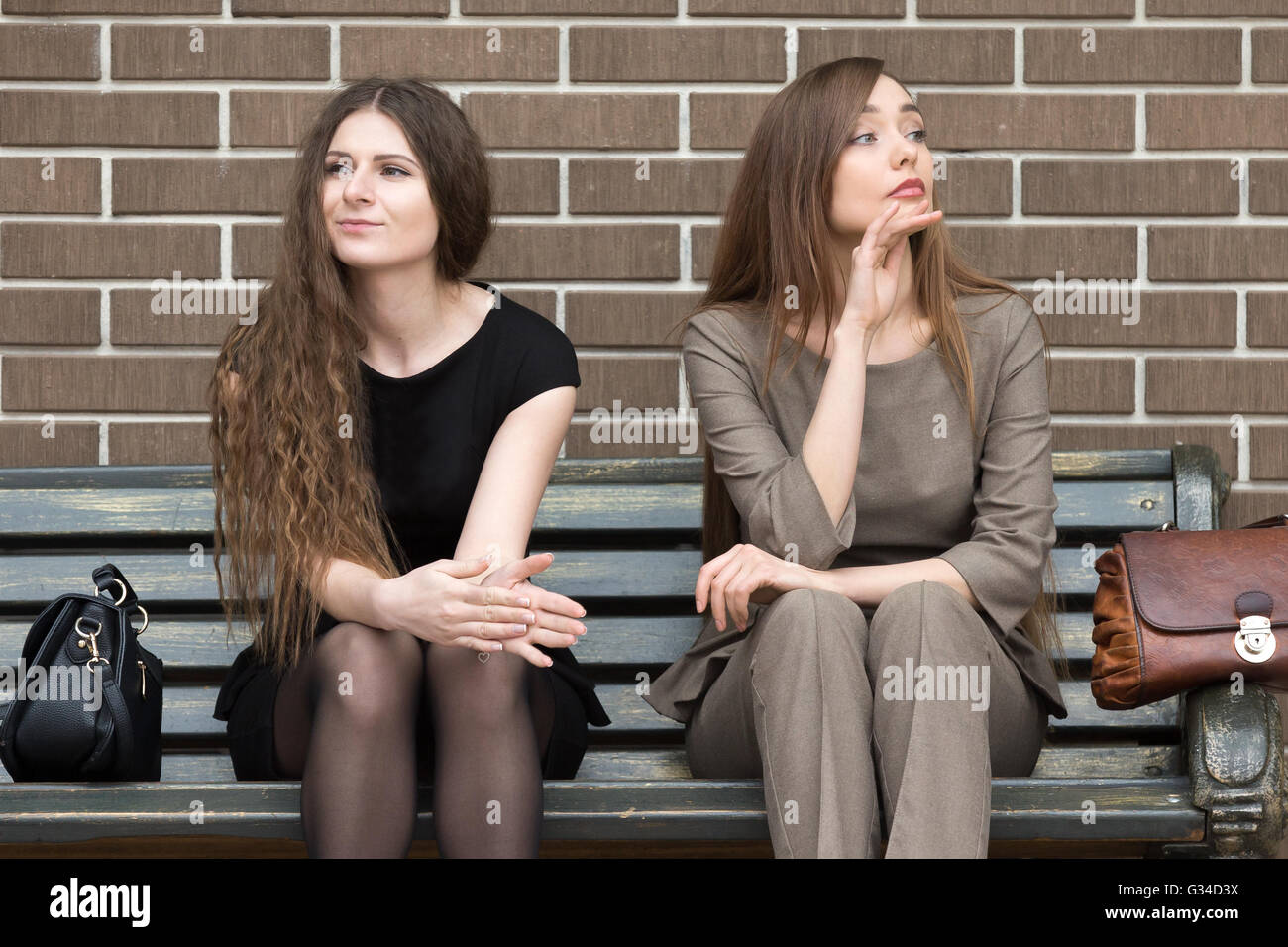 Full length portrait of two beautiful young female rivals sitting side by side on bench. Attractive caucasian office - Stock Image