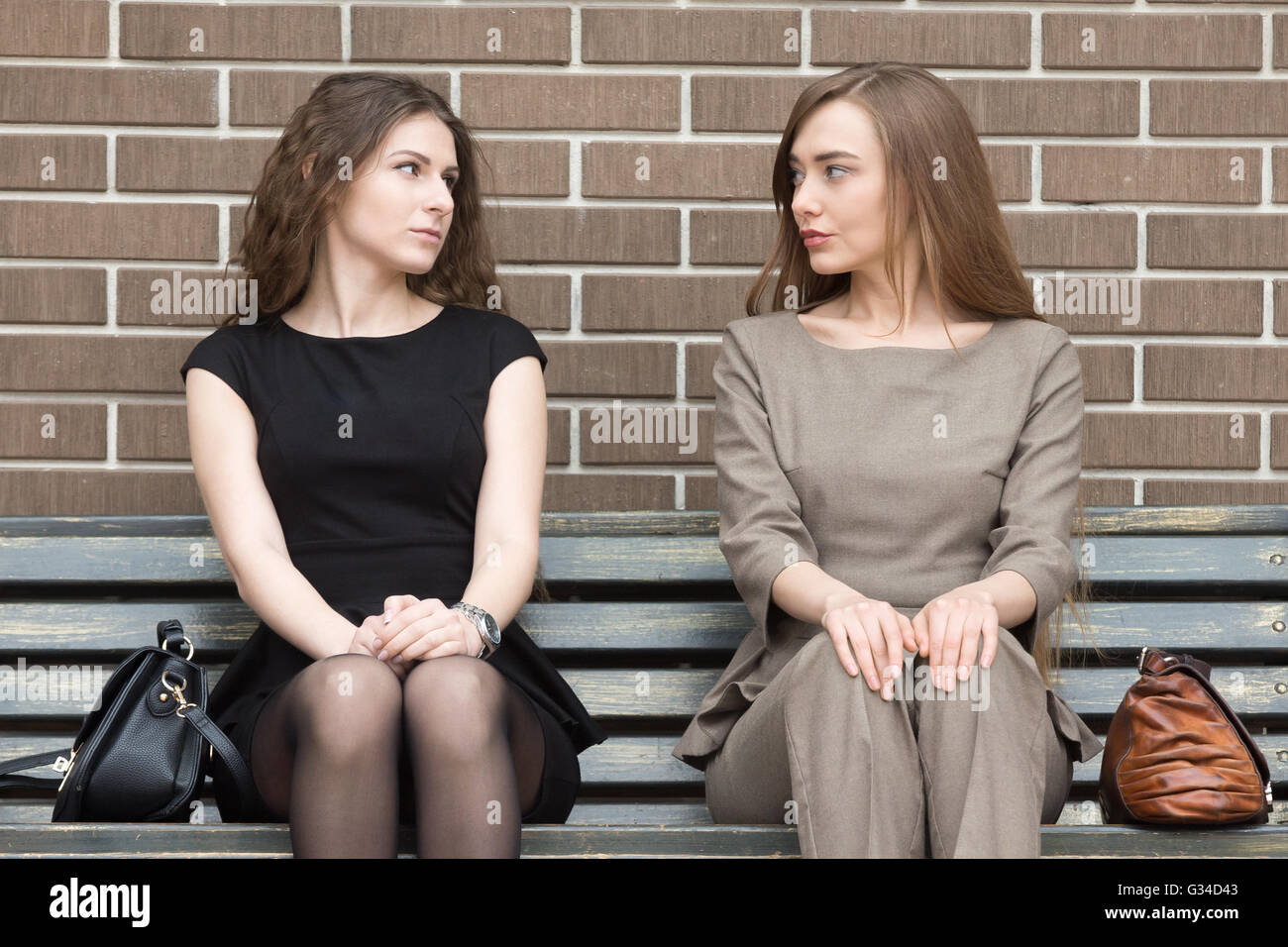 Portrait of two beautiful young female rivals sitting side by side on bench and looking at each other with challenging - Stock Image