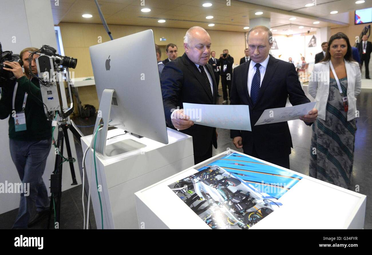 Russian President Vladimir Putin views photographs with RIA Director General Dmitry Kiselev during a visit to the - Stock Image