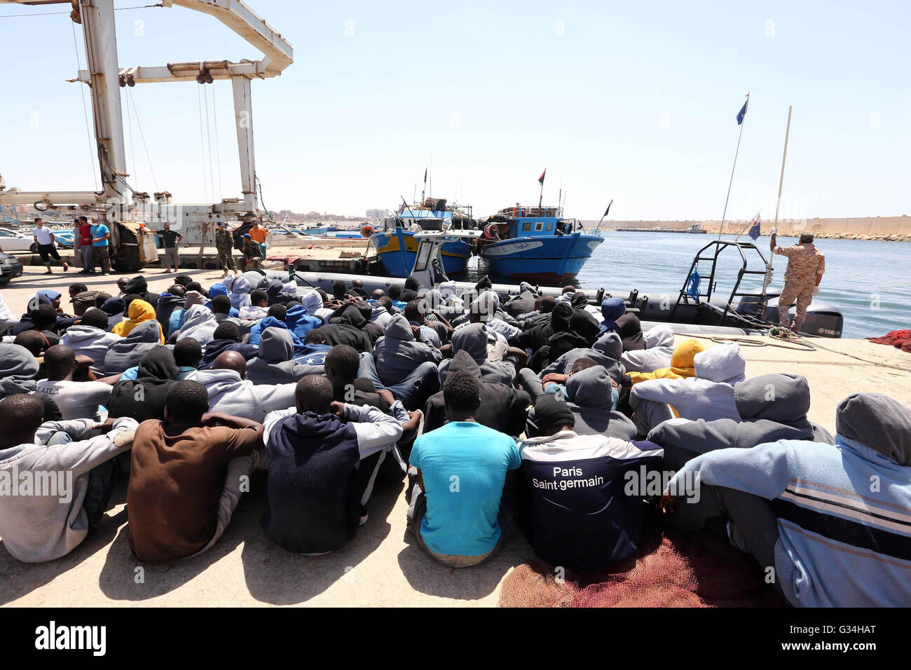 Tripoli. 7th June, 2016. Illegal migrants sit on the dock at the Tripoli port in Tripoli, Libya on June 7, 2016. - Stock Image
