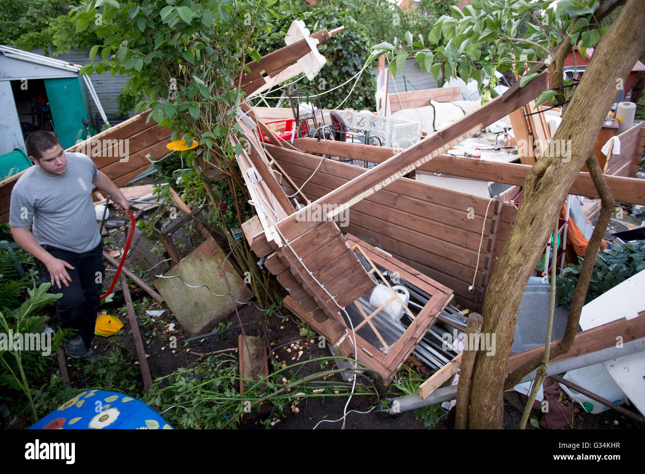 Dominic stands in the remains of an arbour that was destroyed by severe weather in Hamburg, 7 June 2016. Hamburg's - Stock Image
