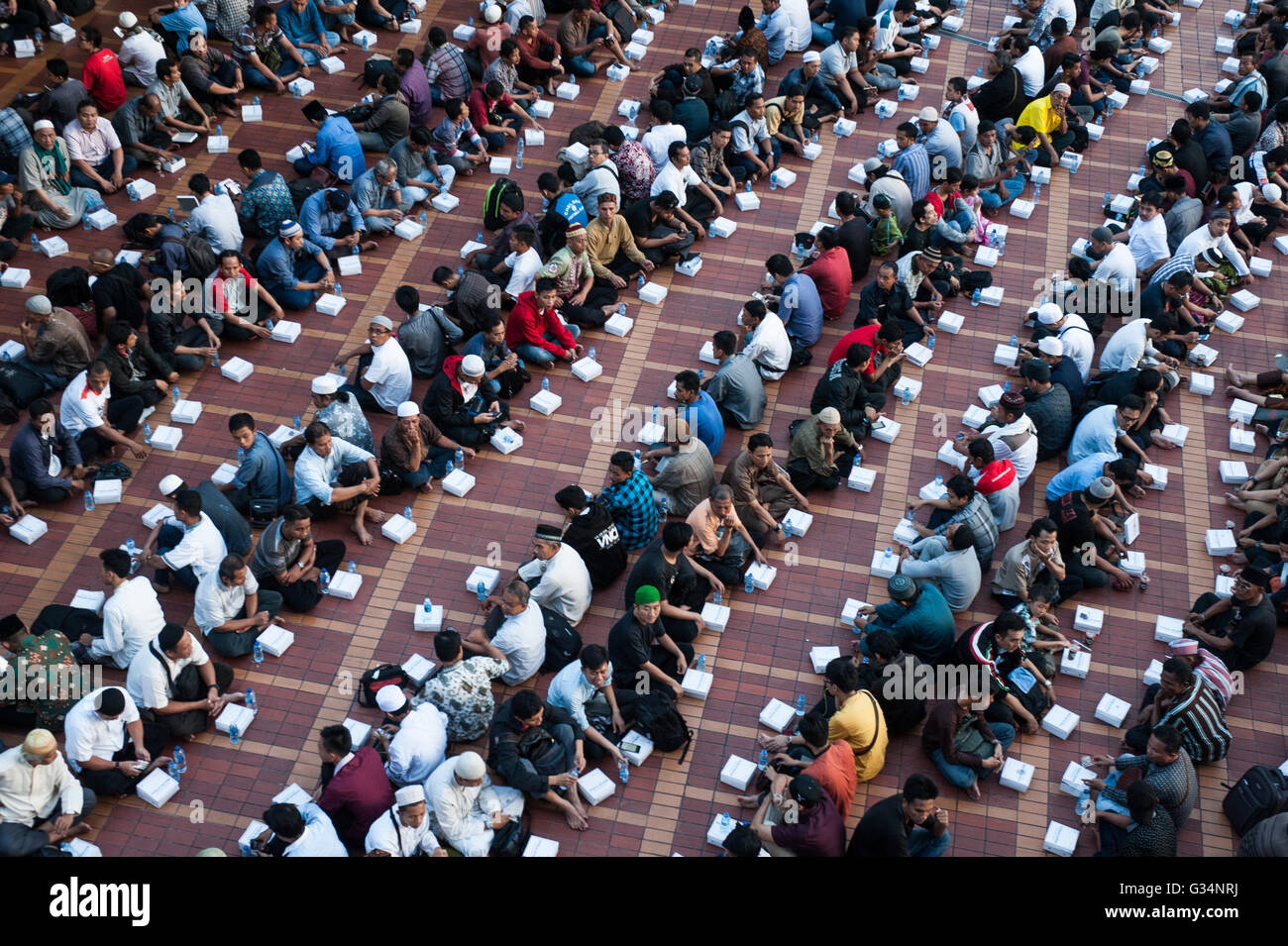 Jakarta, Indonesia. 8th June, 2016. Indonesian Moslems gather and sit in rows while waiting Iftar meal time at the - Stock Image