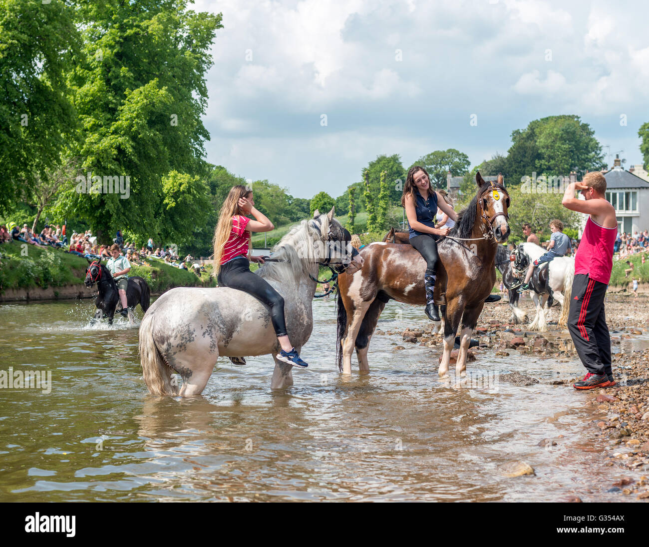 Travellers washing riding their horses in the river Eden at Appleby Horse Fair, Cumbria, UK. 2016 - Stock Image