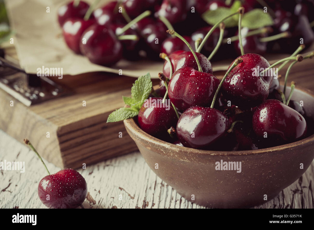 Sweet cherries  in ceramic bowl on wooden background,  retro style, grained, selective focus - Stock Image