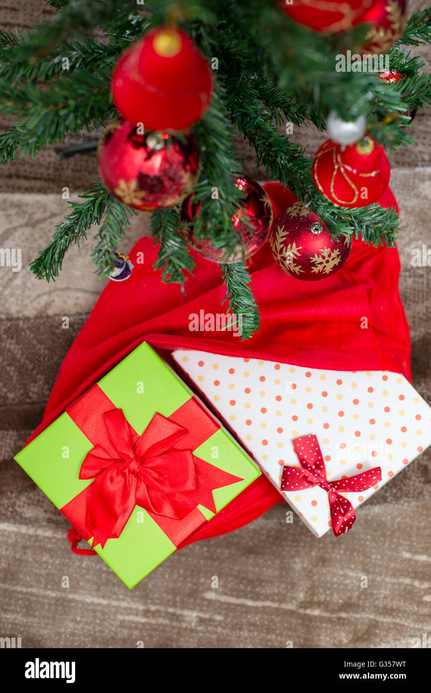 Christmas tree with gift box and decorations on wooden background space for lettering - Stock Image