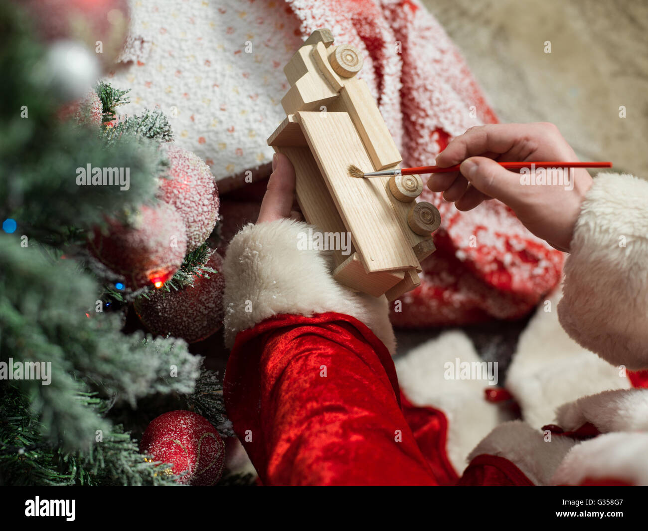 Santa Claus painting wooden toy with gouache - Stock Image