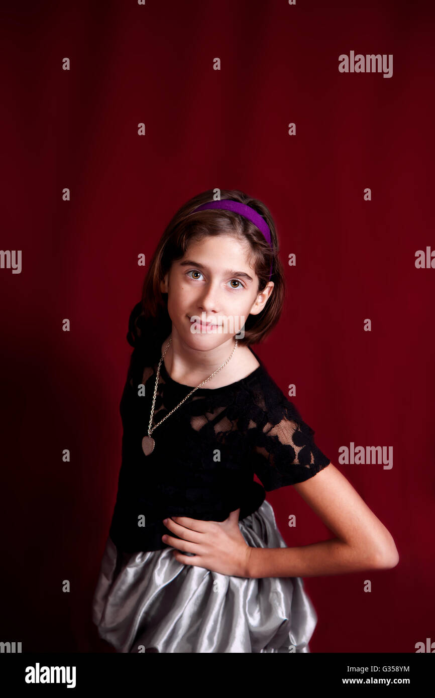Studio portrait of a young, tween girl on a red background.  She confidently leans towards the camera with a knowing - Stock Image