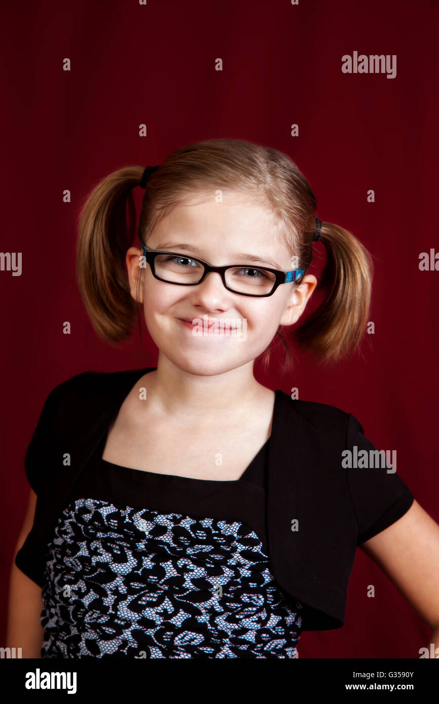 Studio portrait of a girl on a red background. The girl is wearing glasses and has ponytails. - Stock Image