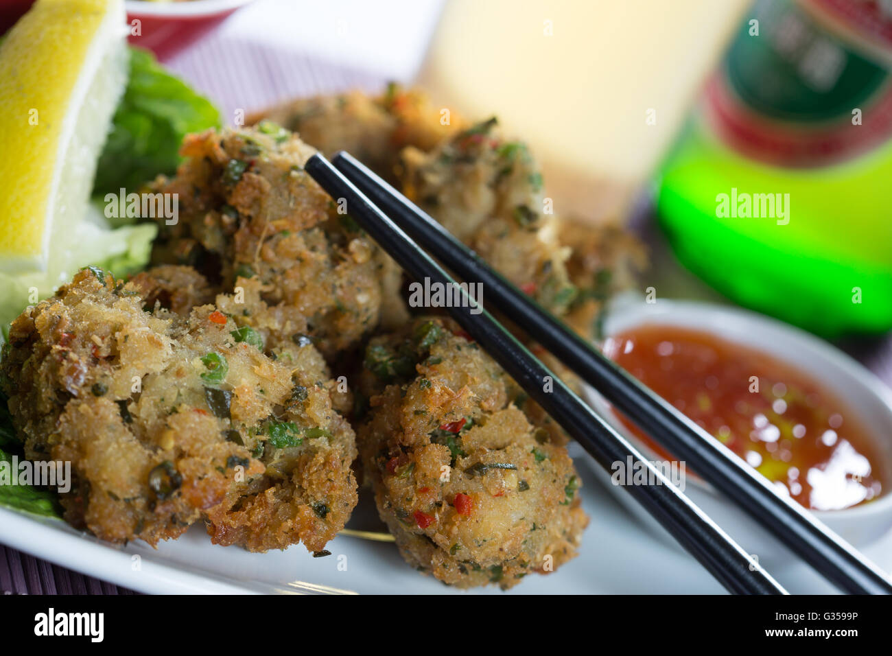 A Traditional Serving Of Thai Fish Cakes Tod Man Pla Presented With An Accompaniment Cuber Relish And Glass Beer