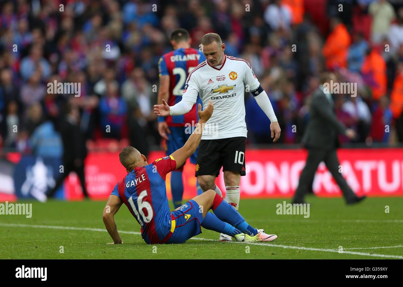 Wayne Rooney of Manchester United helps Crystal Palace's Dwight Gayle off the pitch after the Emirates FA Cup Final - Stock Image