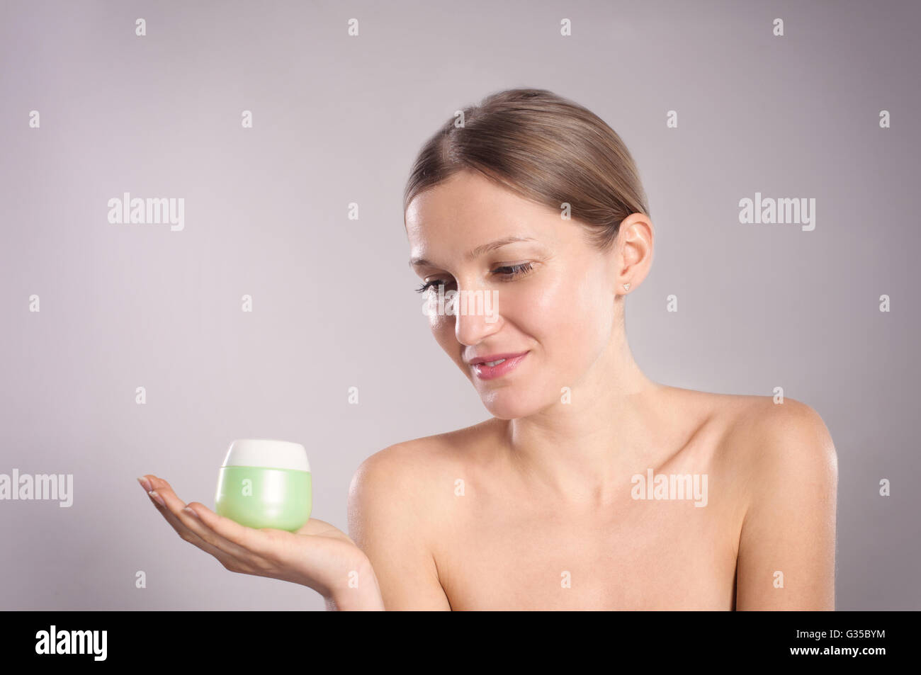 Happy young woman holding her favorite face cream - Stock Image
