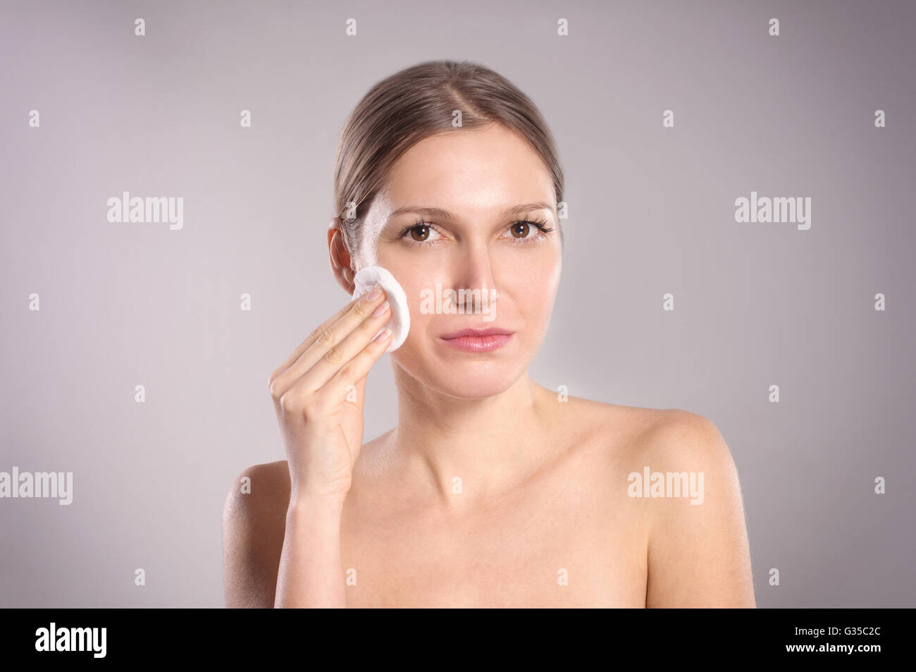 Beautiful woman cleaning her face with cotton swab - Stock Image