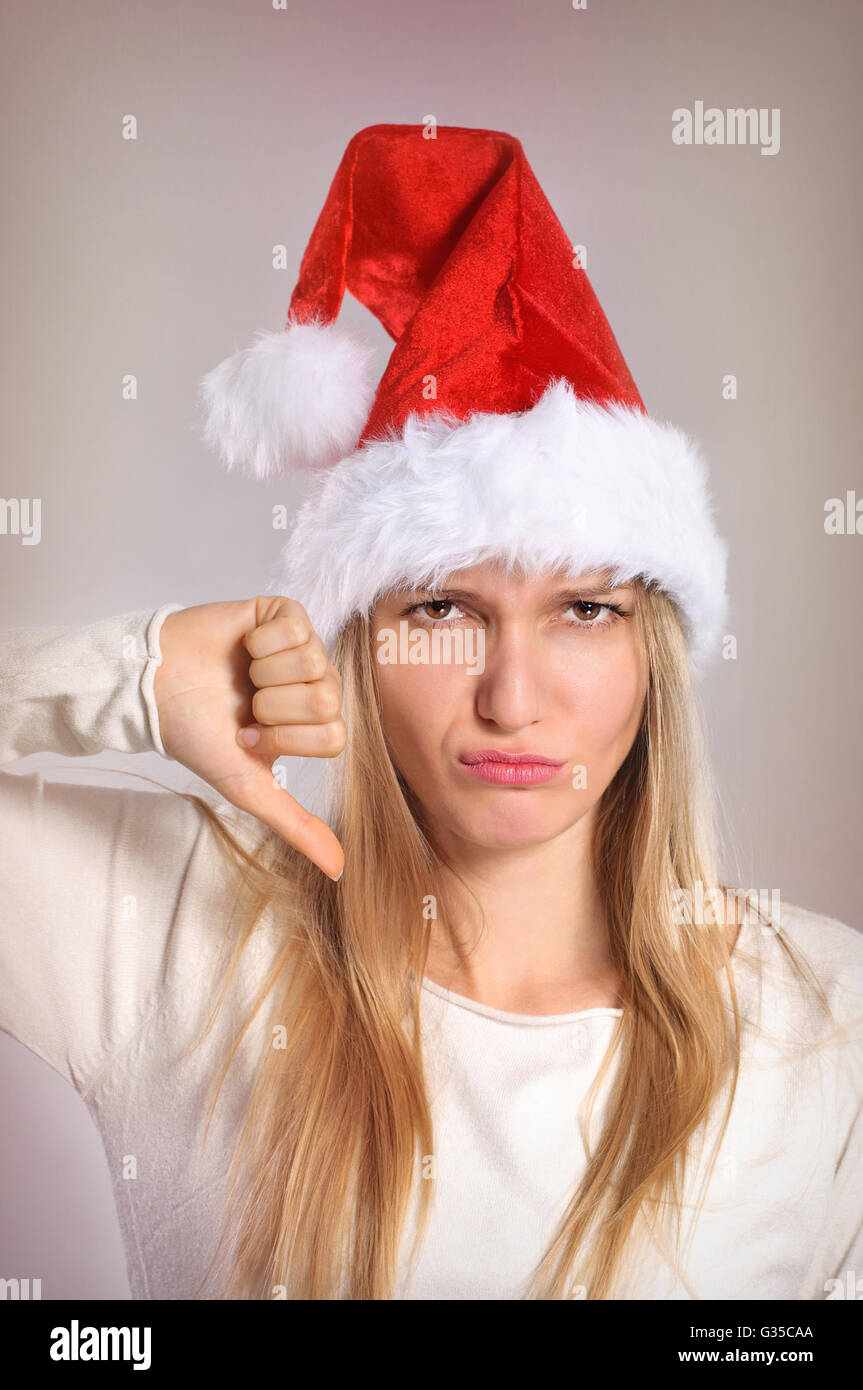 Beautiful Christmas woman with thumbs down sign. Disappointed girl with Santa hat - Stock Image