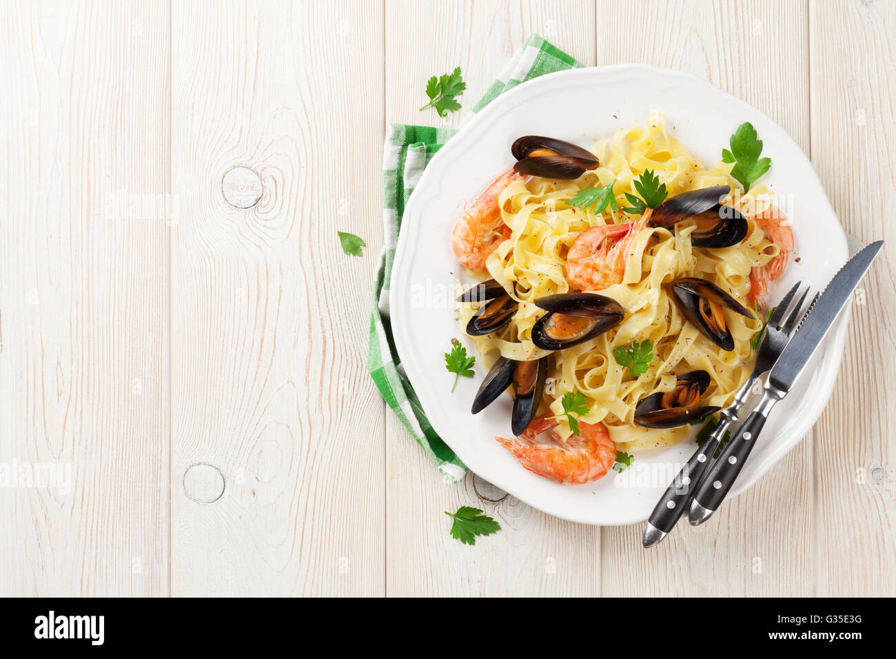 Pasta with seafood on wooden table. Mussels and prawns. Top view with copy space - Stock Image