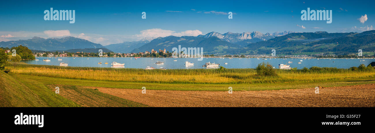 Beautiful panoramic view of boats lying in Lake Zurich with the historic town of Rapperswil in the background in - Stock Image