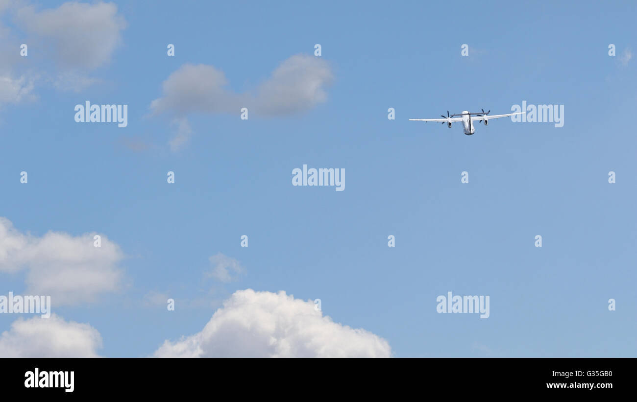White airline commuter airplane taking off into a blue sky with white puffy clouds - Stock Image