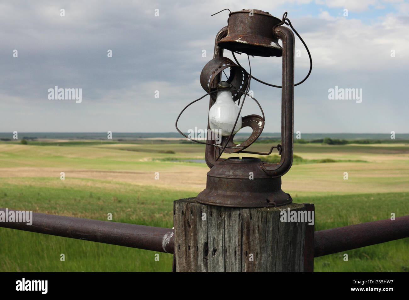 Antique lantern on a fence post on a farm in Alberta, Canada. - Stock Image
