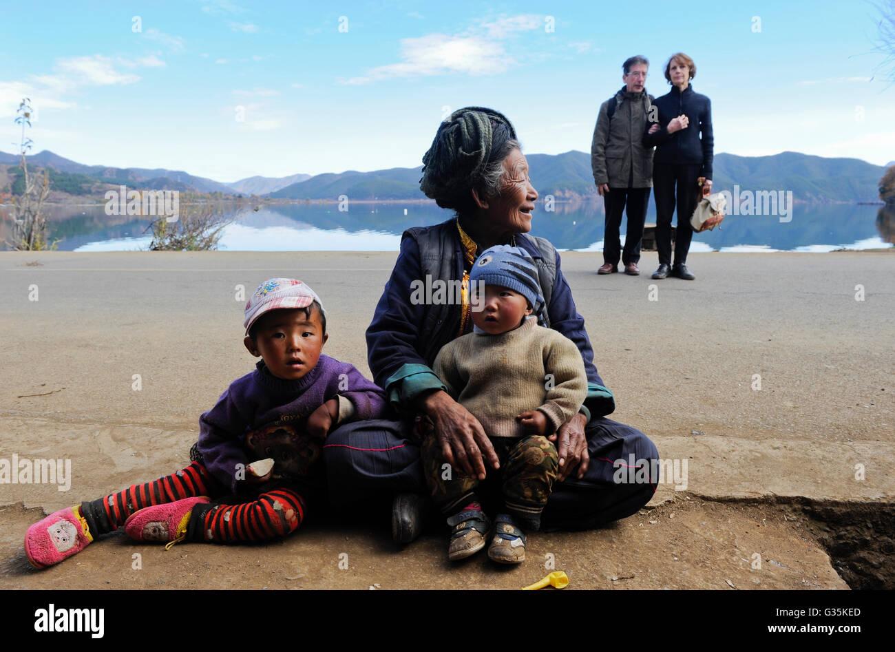 CHINA Provinz Yunnan ,franzoesische Touristen und  ethnische Minderheit Naxi am Lugu See , die Naxi sind Buddhisten - Stock Image