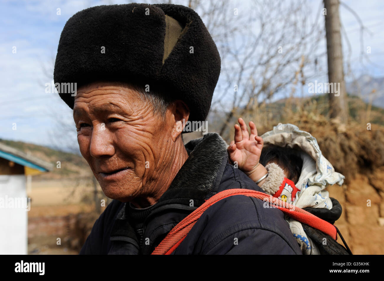 CHINA Yunnan Lugu Lake , ethnic minority Mosuo who are buddhist and women have a matriarch, Mosuo man with animal - Stock Image