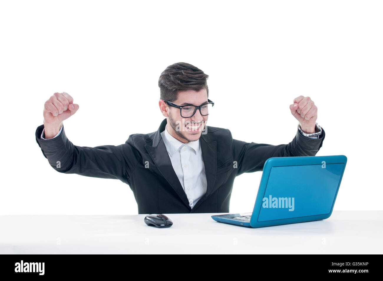 Young man with raised fists using laptop. Isolated on white background - Stock Image