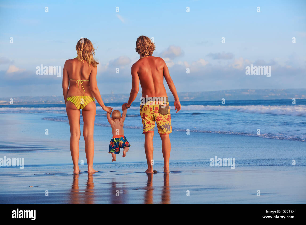 Happy family - father, mother, baby son hold hands, swim with fun, walk along sunset sea surf on black sand beach. - Stock Image