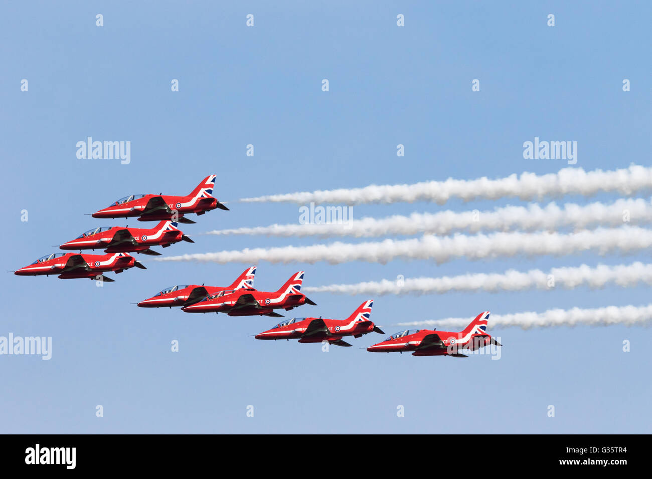Seven members of the RAF Red Arrows aerobatic display team flying in formation with smoke, Duxford American Airshow, - Stock Image