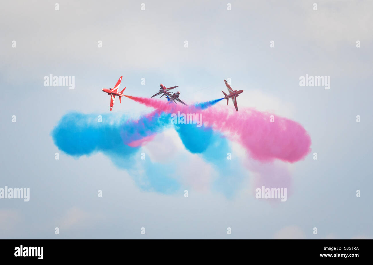 Red Arrows RAF aerobatic team performance, doing a crossover with colourful smoke, Duxford airshow, Cambridgeshire - Stock Image
