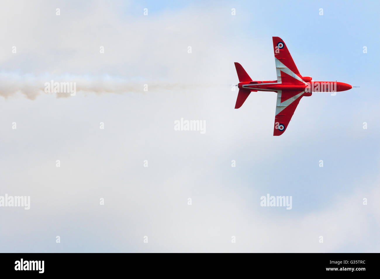 Red Arrows plane flying straight, with white smoke, Duxford Airshow, Cambridgeshire UK - Stock Image