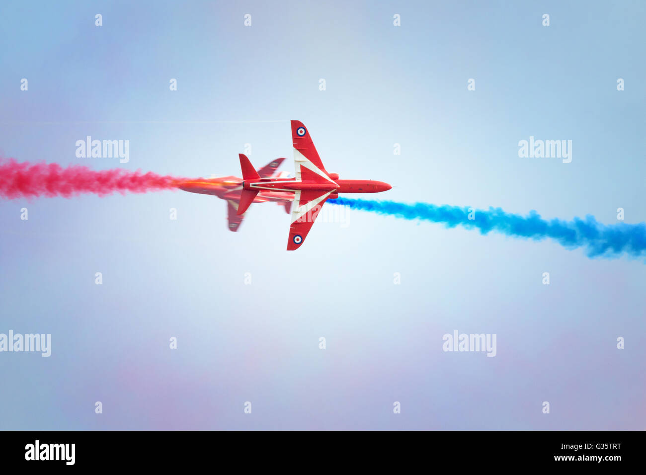 Red Arrows RAF aerobatic team performing a crossover with coloured smoke ; Duxford Airshow, Duxford Cambridgeshire - Stock Image