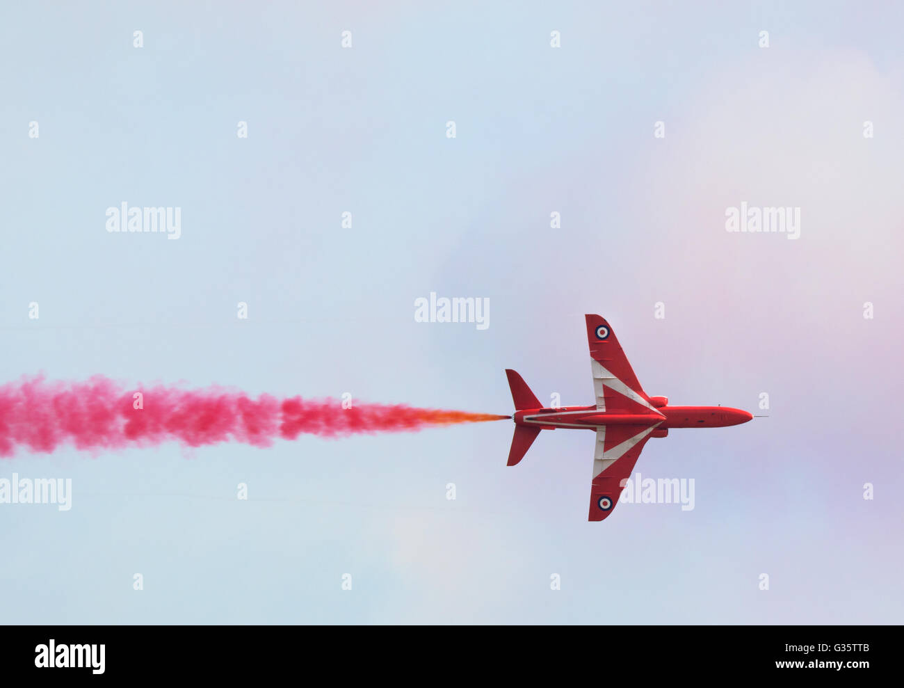 Red Arrows plane flying straight, with colourful red smoke, Duxford Airshow, Cambridgeshire UK - Stock Image