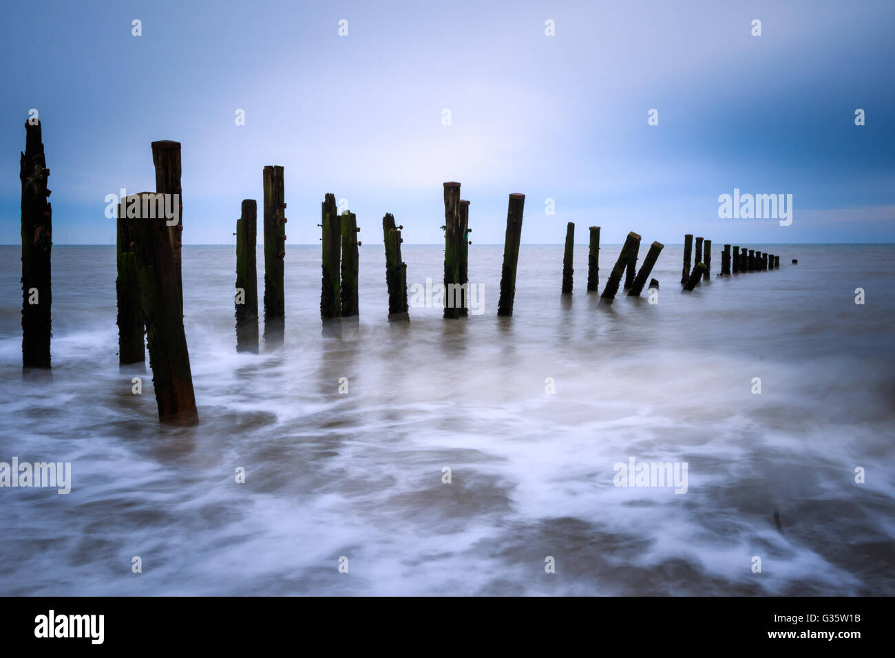 Wooden groynes on the beach with long exposure. - Stock Image