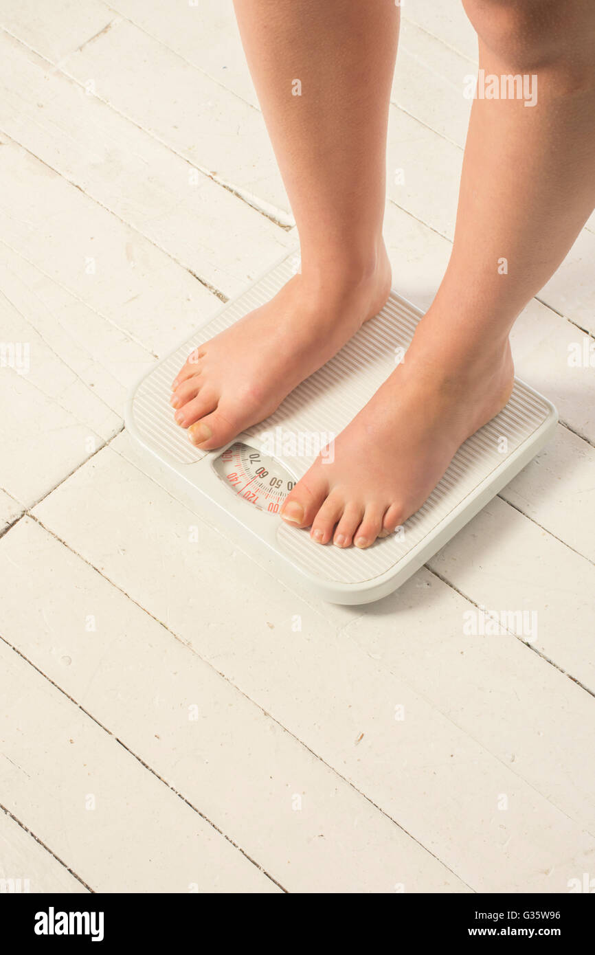 Barefooted woman standing on the scale measure her bodyweight - Stock Image