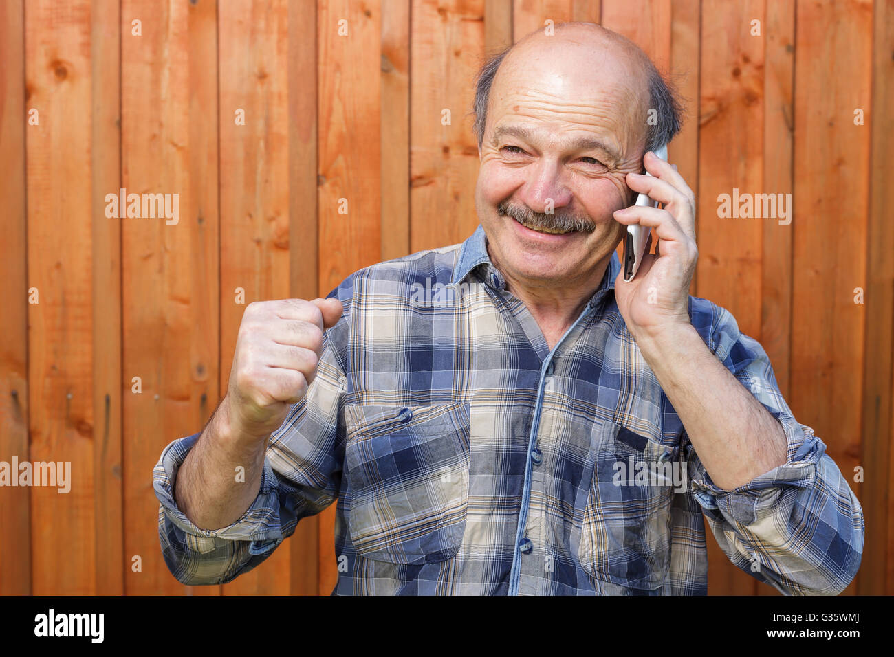 Elderly man talking on the phone. Maintaining family ties at a distance. Order by phone - Stock Image