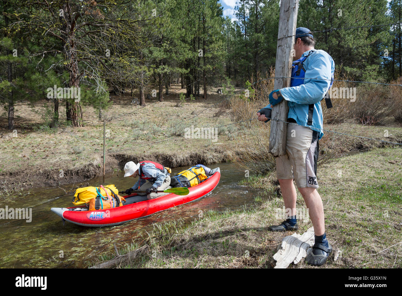 Kayaker lifting a barbed wire fence so that another kayaker can paddle underneath on the headwaters of the North - Stock Image