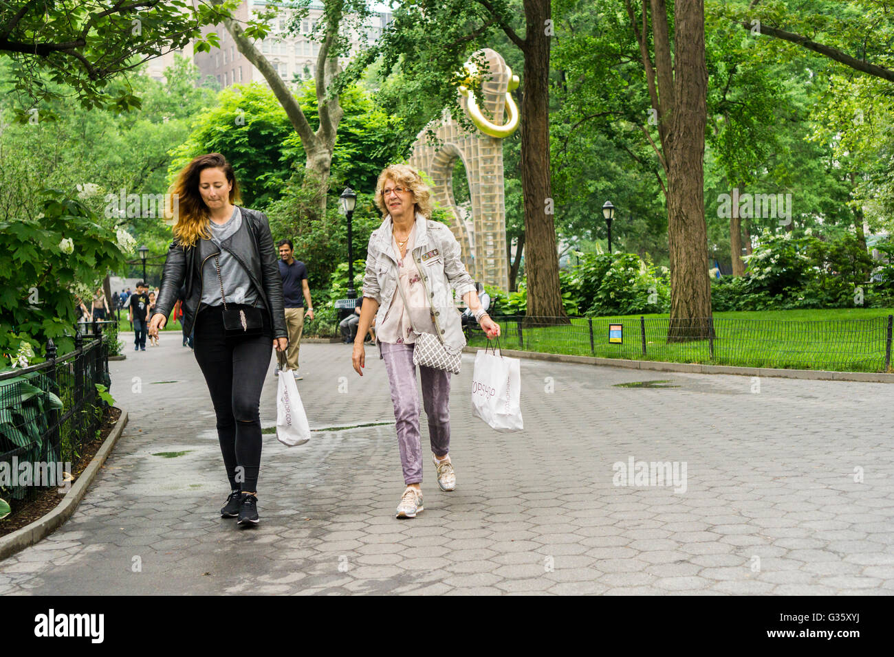 Shoppers with their purchases pass through Madison Square Park in New York on Sunday, June 5, 2016.  (© Richard - Stock Image