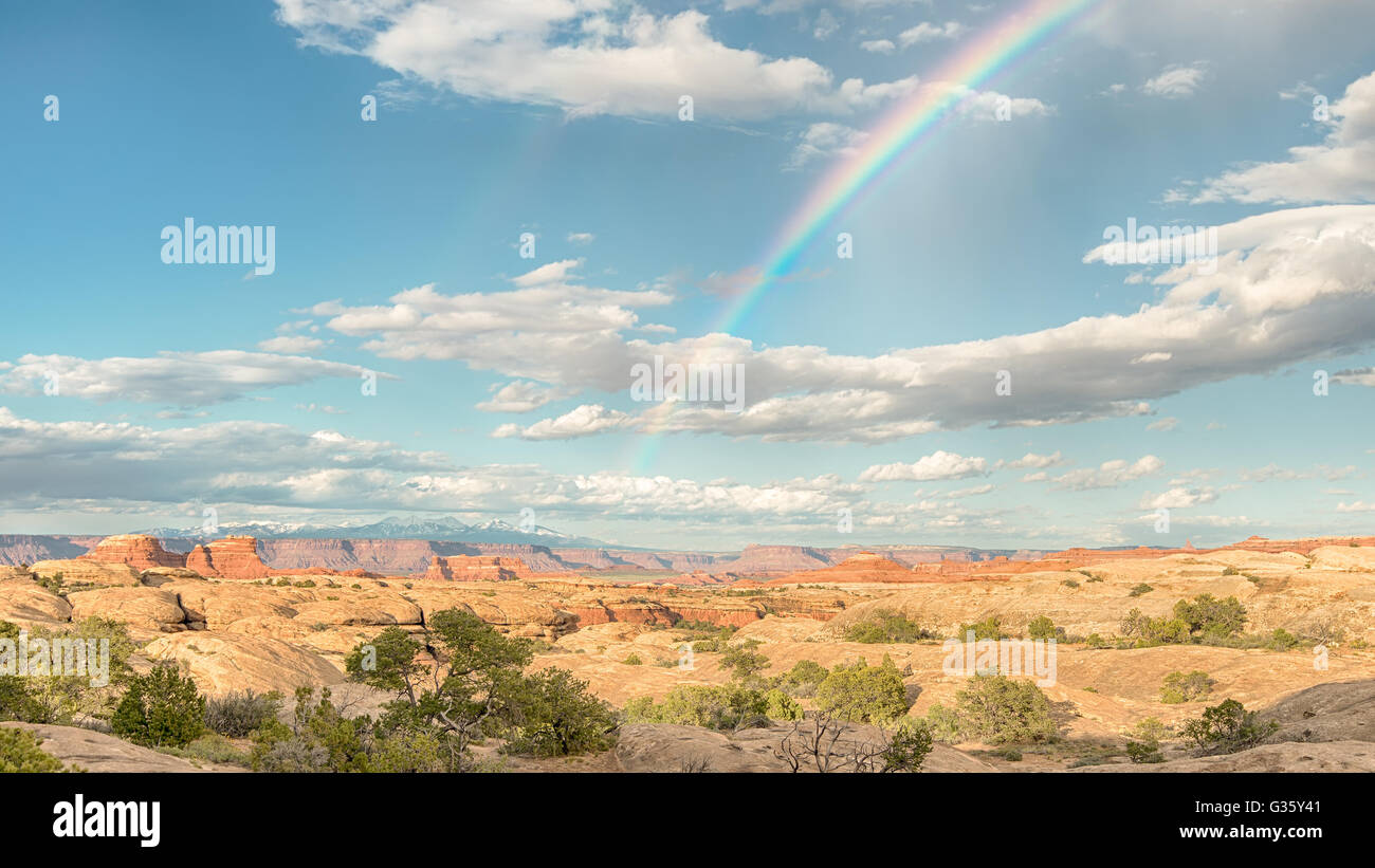 A rainbow arcs across the sky towards the La Sal mountains, in the Needles District of Canyonlands National Park, - Stock Image