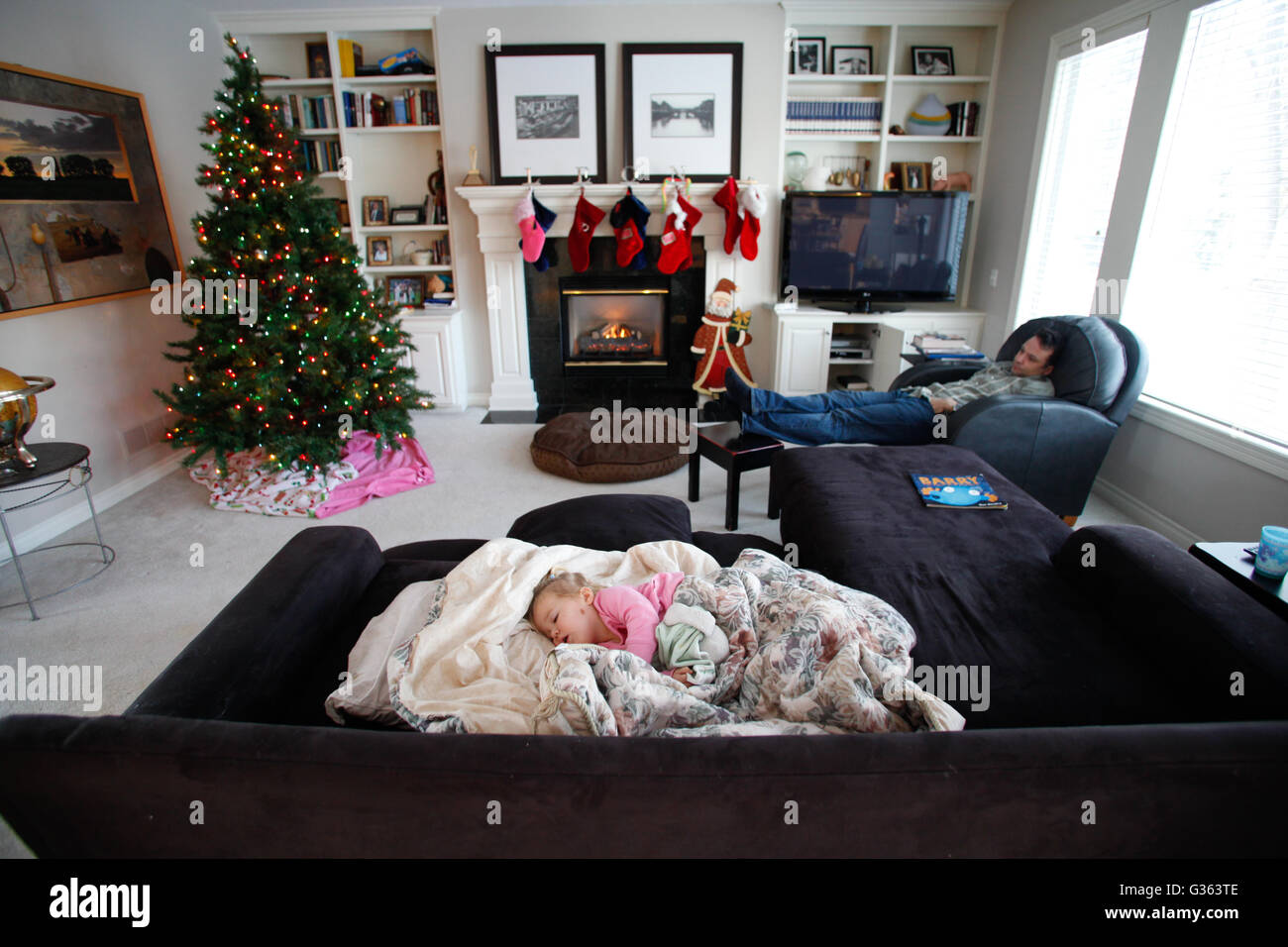 A man and a child sleep in a living room, which is decorated ...