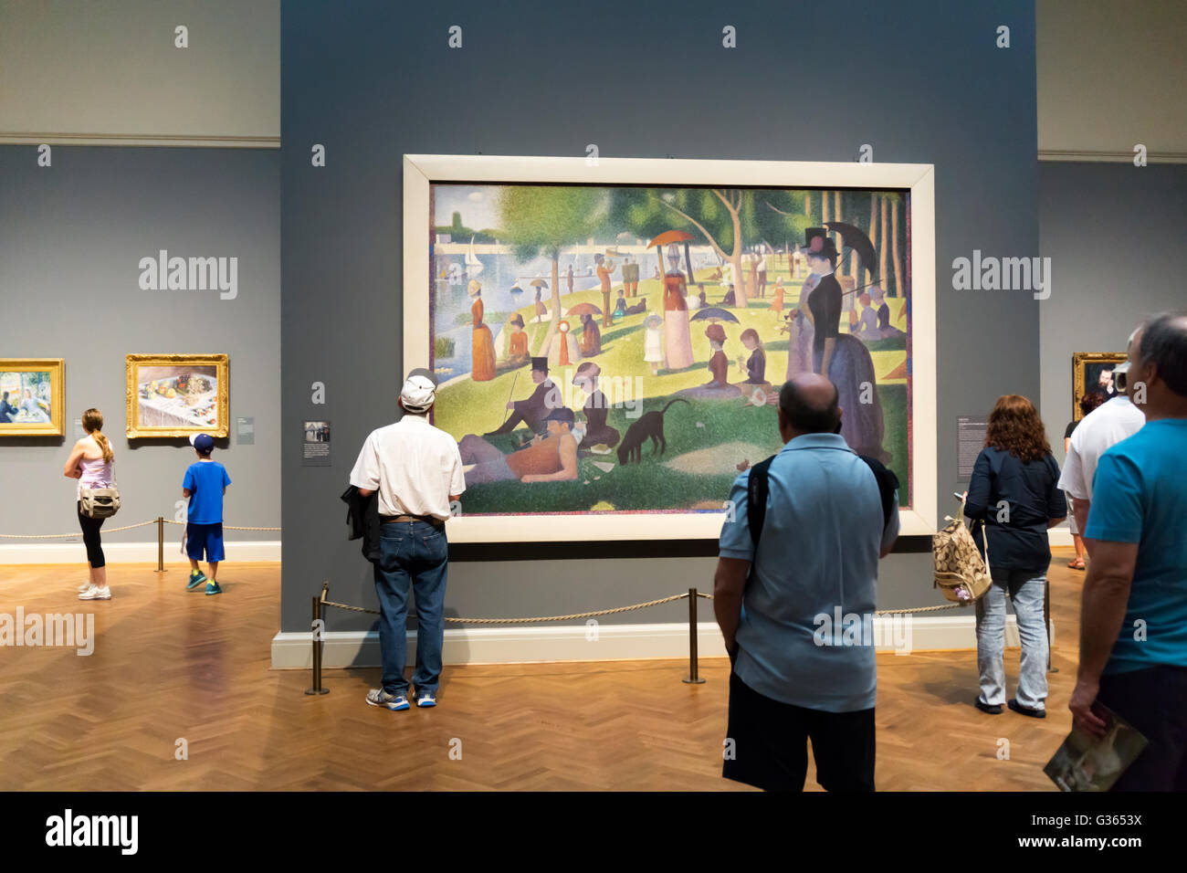 Visitors admiring A Sunday Afternoon on the Island of La Grande Jatte – 1884 by Georges Seurat in the Art Institute - Stock Image