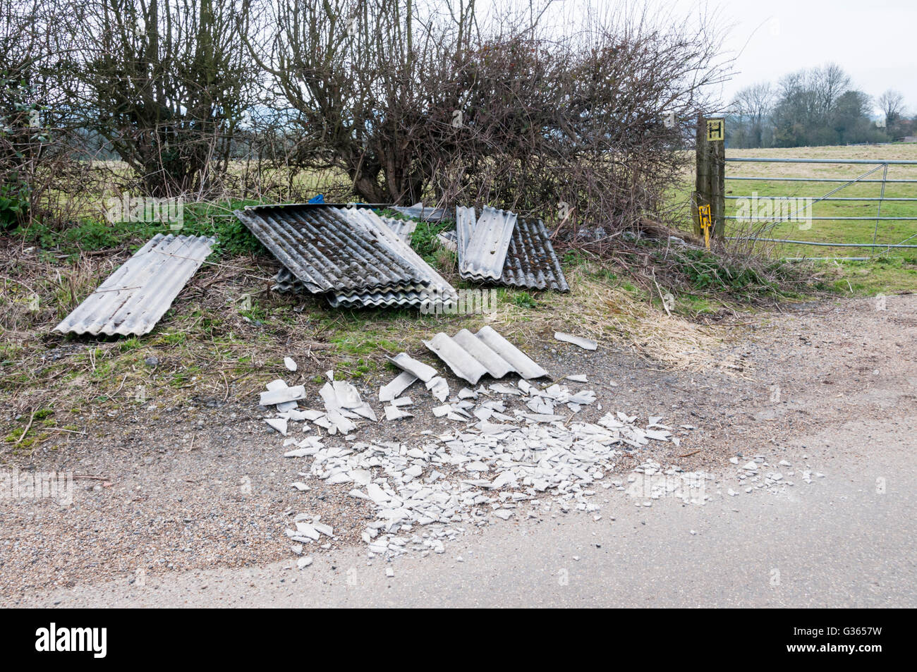 Waste asbestos sheeting dumped in a country lane. - Stock Image