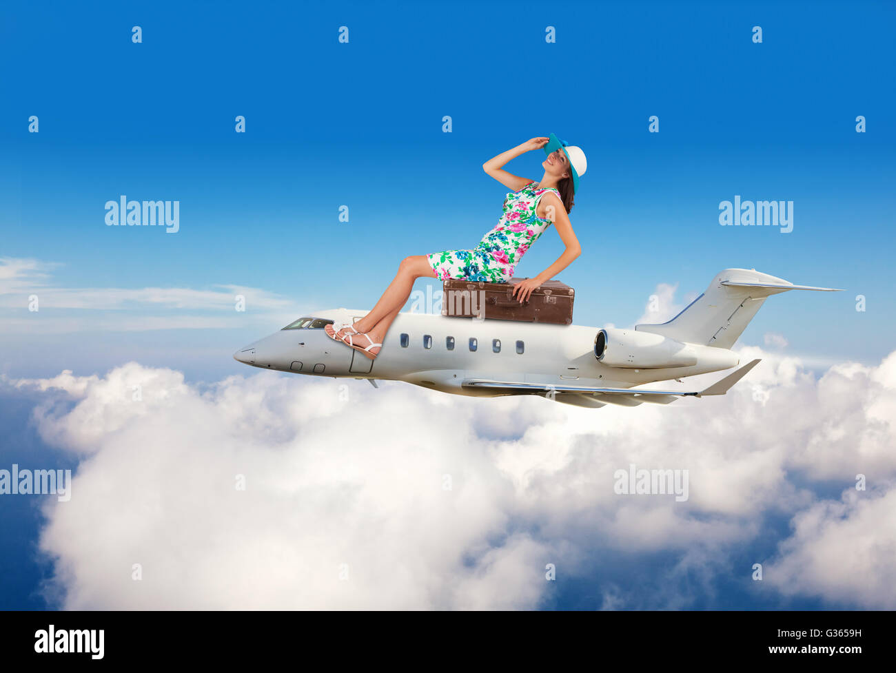 Young woman sitting on airplane, flying above clouds. Concept of traveling and summer vacation - Stock Image
