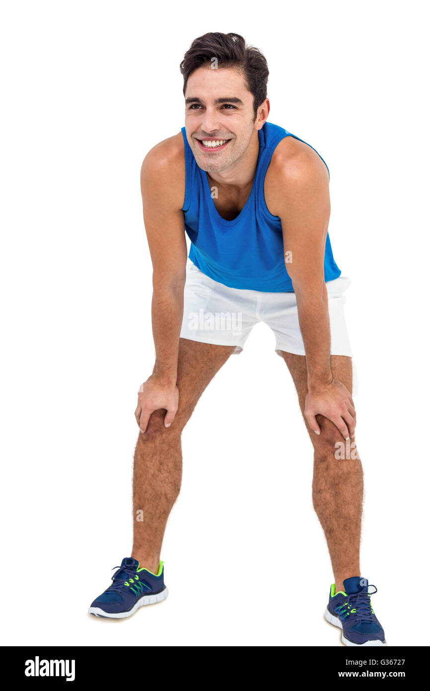 Male athlete standing with hand on knee Stock Photo