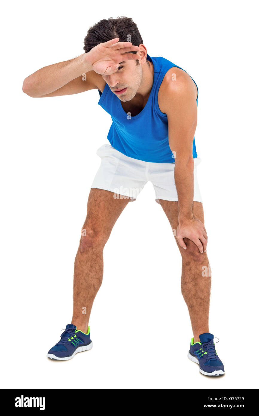 Tired athlete wiping his sweat with hand - Stock Image