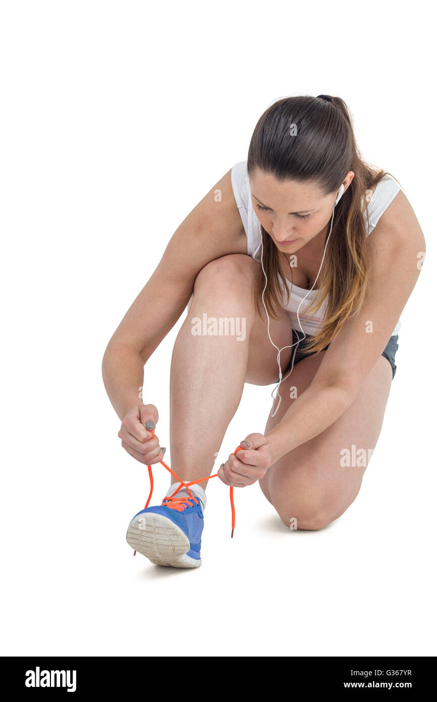 Athlete woman tying her running shoes Stock Photo