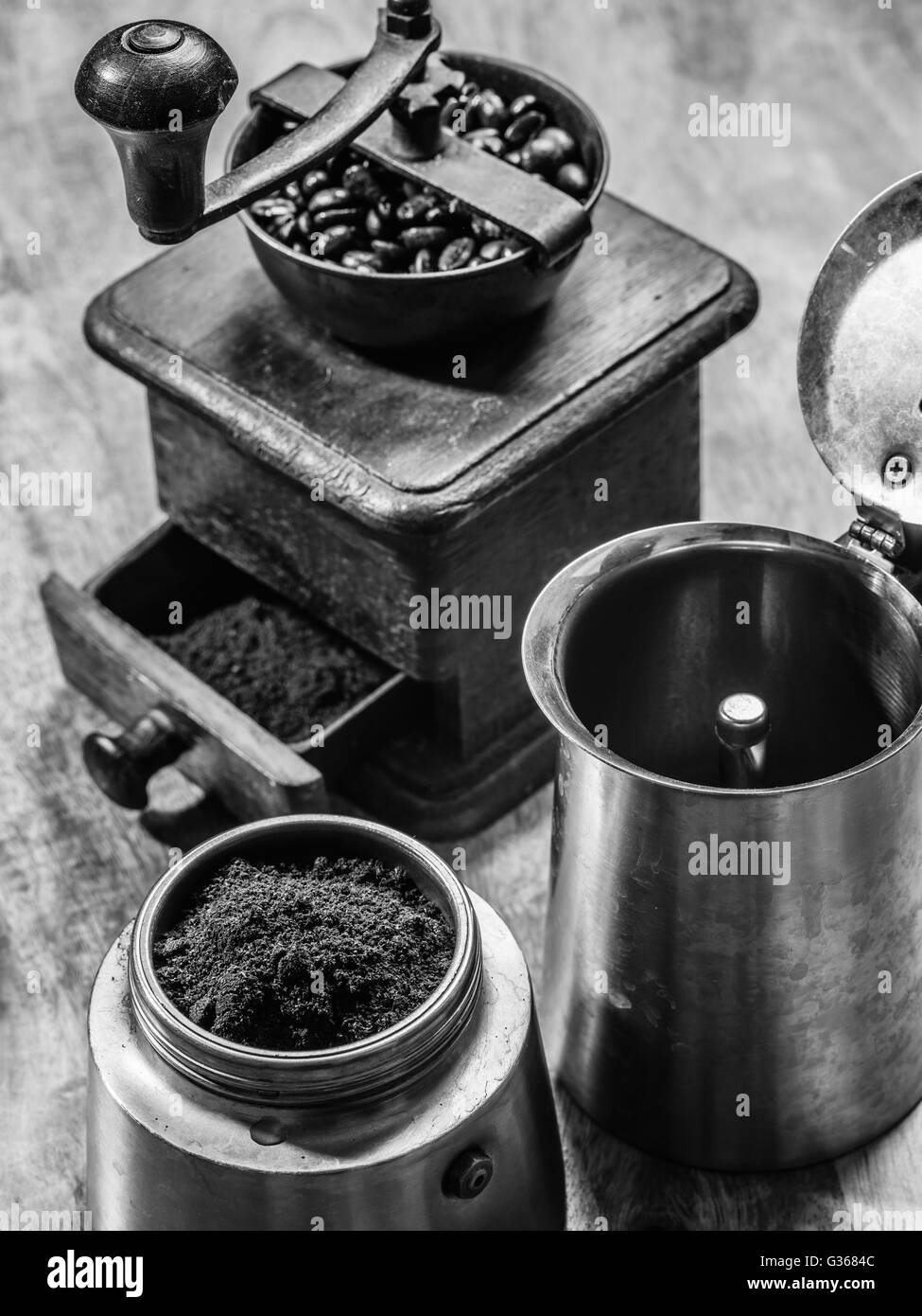 Photo of an Italian Moka Express stovetop coffee maker and a coffee grinder done in black and white. - Stock Image
