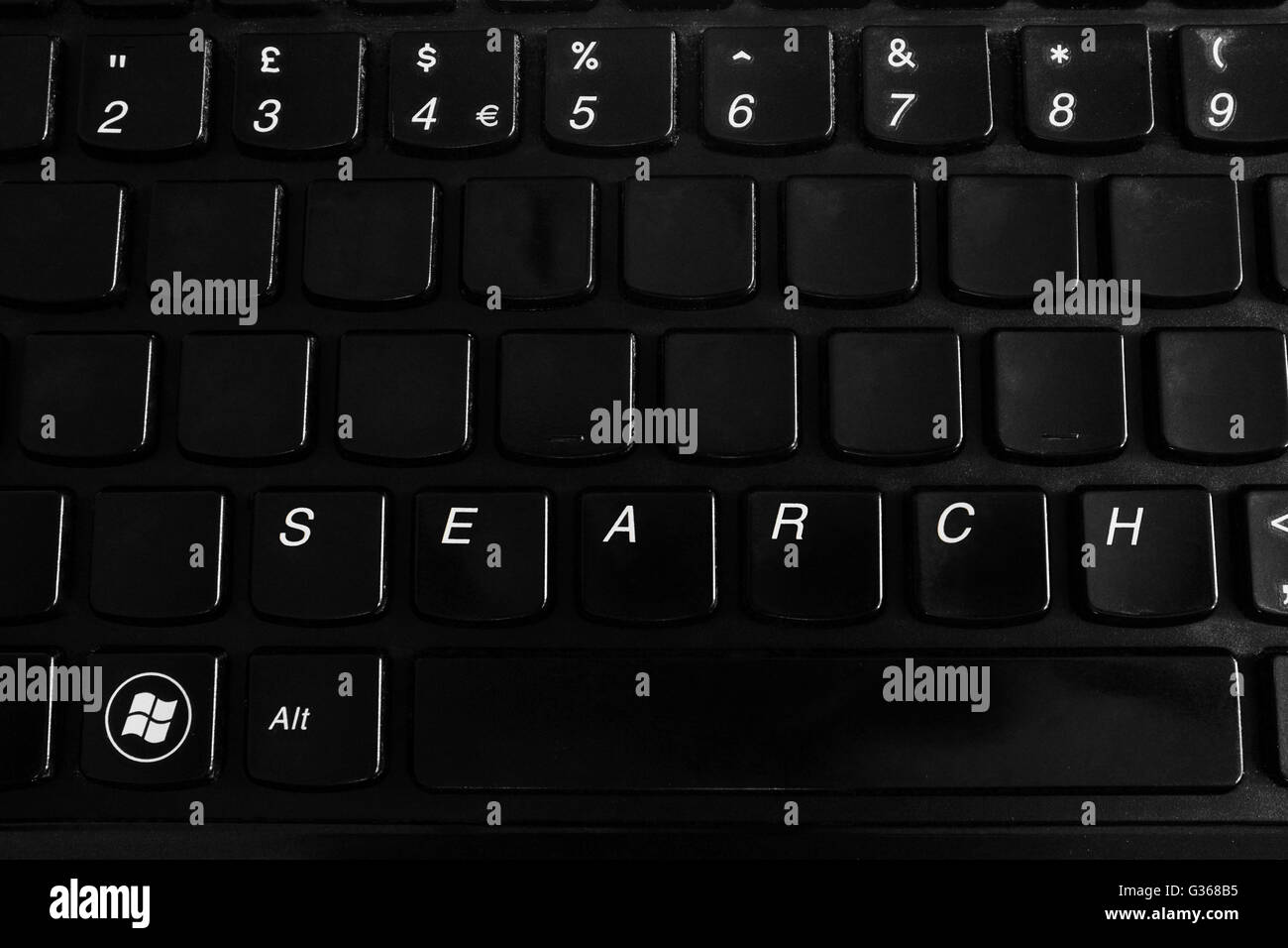 A black laptop keyboard with search on it. - Stock Image