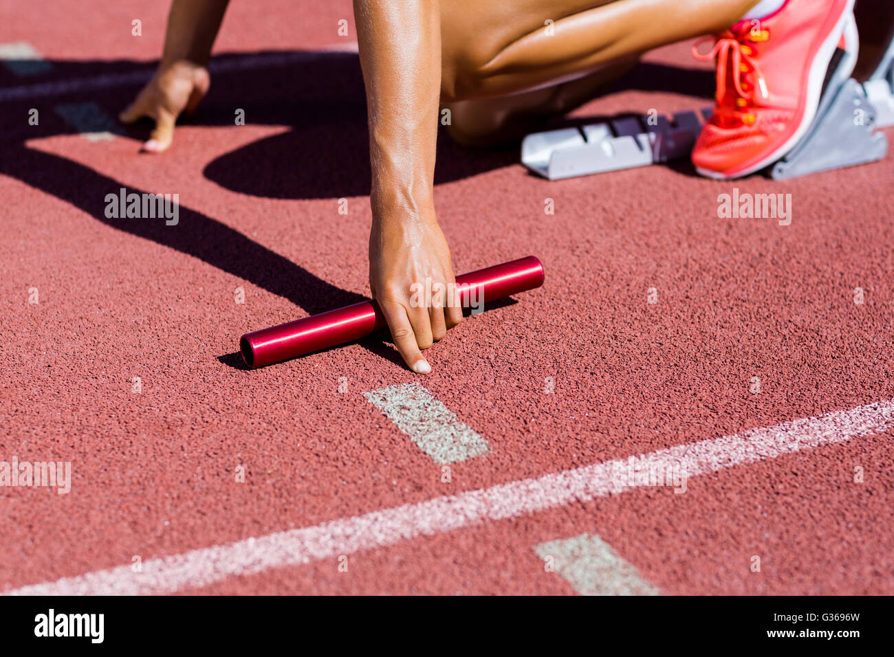 Female athlete ready to start the relay race - Stock Image