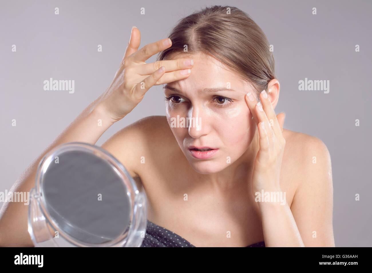 Woman checking her wrinkles on her forehead - Stock Image